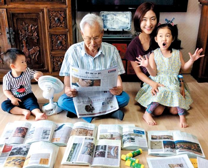 김연홍(86·가운데)씨가 두 증손주에게 스크랩해 놓은 조선일보 기사들을 보여주고 있다.