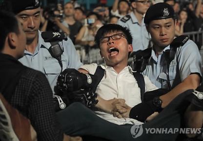 홍콩 민주주의 운동가 조슈아 웡이 28일 홍콩 골든 바우히니아 광장에서 반중시위를 벌이다 홍콩 경찰에 의해 강제연행되고 있다. /AP연합뉴스