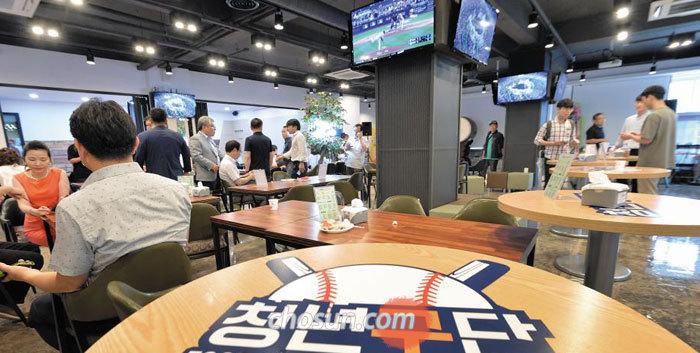 대전 시민들이 야구를 테마로 한 스포츠 펍 형태 청년몰'청년구단'에서 TV로 경기를 보며 음식을 먹고 있다.