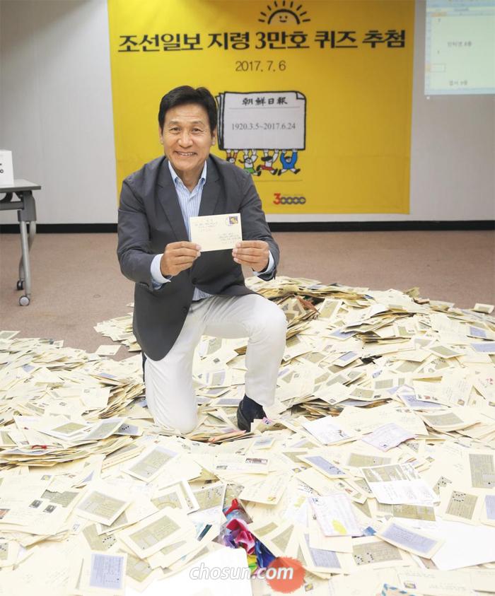 배우 안성기씨가 6일 서울 광화문 조선일보 사옥에서 '지령 3만호 퀴즈'에 응모한 11만여 통 엽서 중 1등 당첨 엽서를 들어 보이고 있다.