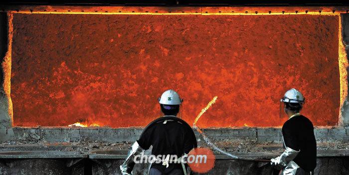 근로자들이 700도가 넘는 용해로 앞에서 합금 용액에 질소 가스를 불어 넣기 위해 호스의 위치를 조정하고 있다.
