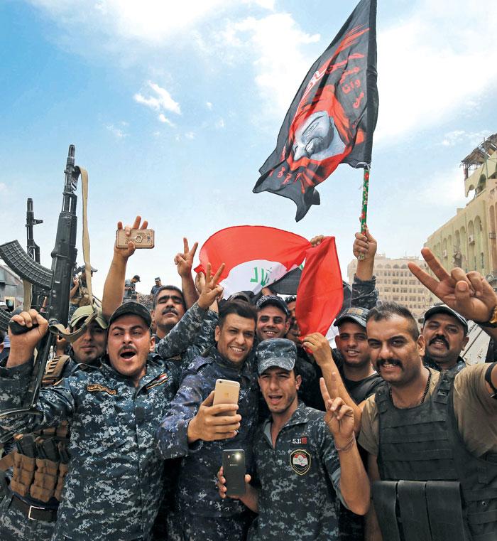 9일(현지 시각) 이라크 경찰들이 이라크 북부 모술 도심에서 이슬람국가(IS) 격퇴를 자축하고 있다.