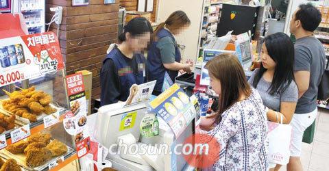16일 서울 중구의 한 편의점에서 알바생들이 손님들이 건넨 물건 값을 계산하고 있다.