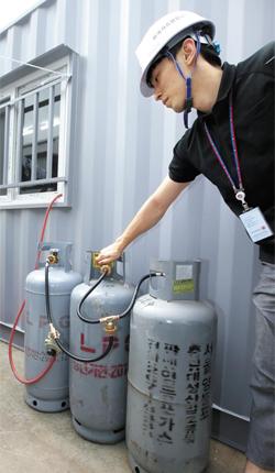 18일 서초구 잠원 한강공원수영장에서 한국가스공사 검침원이 어지럽게 연결된 LPG가스통을 살펴보고 있다.