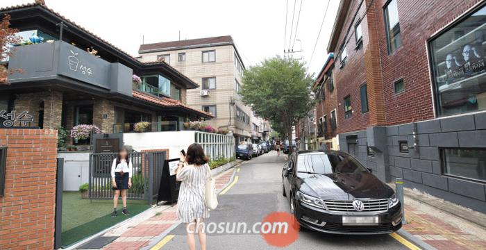지난 14일 오후 서울 성동구 서울숲길의 한 카페 앞에서 사진을 찍는 여성들. 성동구가 다음 달부터 '성수동 카페거리'로 불리는 이곳에 프랜차이즈 업체의 입점을 제한하기로 결정하자 지역 주민들 사이에서도 찬반이 엇갈리고 있다.