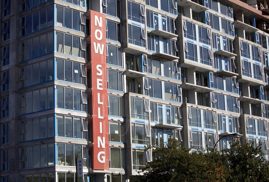 캐나다 밴쿠버는 공실을 막기 위해 올해 1월부터 6개월 이상 빈 주택에 주택 공실세(Empty Homes Tax)를 부과하고 있다. '분양 중' 현수막이 걸린 캐나다 시내의 한 건물. /블룸버그 제공