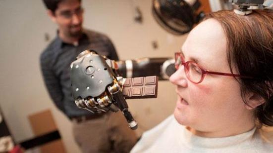 전신마비 환자가 생각으로 로봇팔을 움직여 초콜릿을 먹고 있는 모습. /슈워츠 교수 홈페이지 캡처