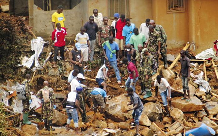 14일(현지 시각) 서아프리카 시에라리온의 수도 프리타운 인근 리젠트 지역에서 발생한 산사태 현장에서 구조대원들이 희생자 수색 작업을 벌이고 있다.
