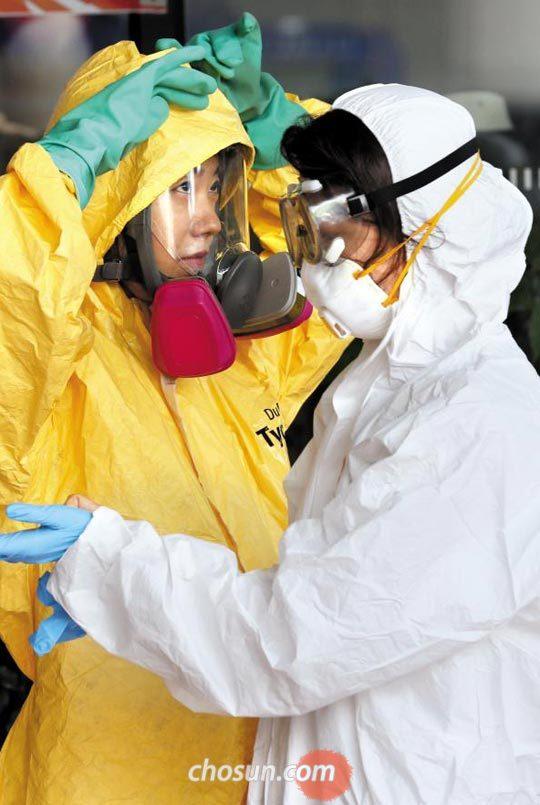 을지프리덤가디언(UFG) 연습이 시작된 21일 오후 경기도 고양시 일산 킨텍스에서 열린 테러·재난 대응 종합훈련 참가자들이 화생방 공격에 대비해 방독면과 장갑 등 장비를 착용하고 있다.