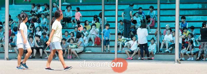 위험에 노출된 아이들 - 23일 오후 2시 민방공 대피훈련이 실시된 서울의 한 초등학교 학생들이 교실에서 나와 운동장 옆 스탠드로 이동해 앉아 있는 모습. 학교가 북한의 장사정포·미사일 공격을 받을 경우 운동장은 가장 위험에 노출되는 곳이다. 반드시 건물 지하나 대피소로 이동해야 한다.