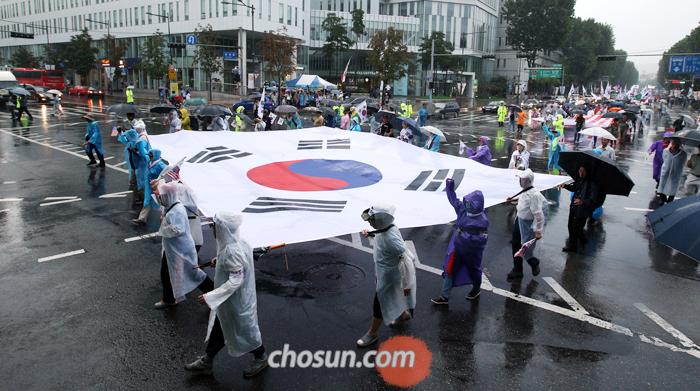 지난 15일 오후 서울 종로구 대학로에 모인 300여개의 보수시민단체 회원들이 대형태극기를 들고 행진하는 모습. 군인권센터는 지난 1월 '태극기 집회'의 주동자 격인 보수시민단체 5명을 내란 선동·명예훼손 혐의로 검찰에 고발했다.