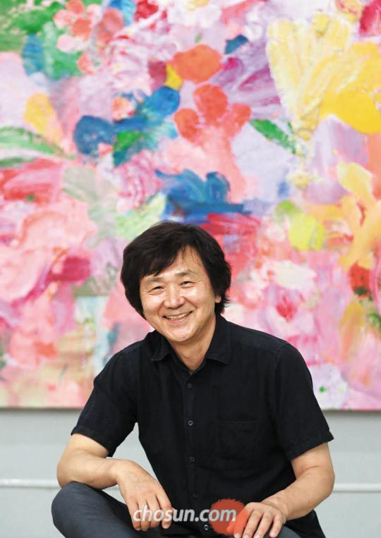 봄날 꽃밭인 것처럼 화사한 색감으로 물결치는 작품 앞에 앉아 있는 이해전 작가.