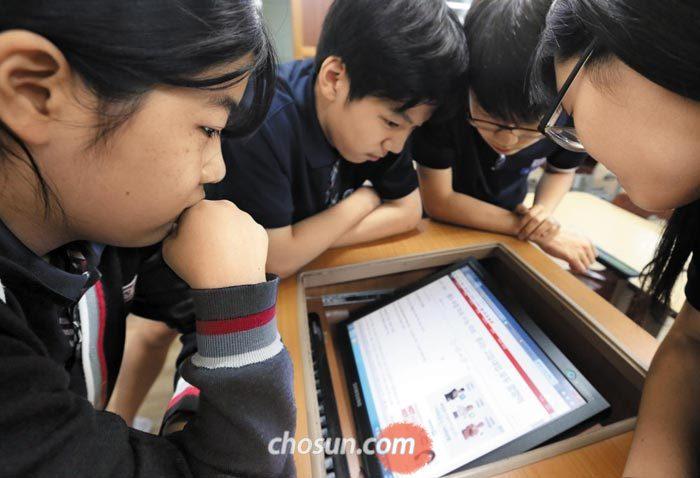 1일 오후 서울 마포구 창천중 3학년 교실에서 학생들이 수능 개편안이 1년 유예됐다는 내용의 인터넷 기사를 심각한 표정으로 읽어보고 있다.