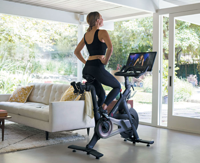 한 여성이 자신의 집에서 헬스케어 스타트업 펠로톤 인터랙티브의 원격 트레이닝 강의를 들으며 실내 자전거를 타고 있다.