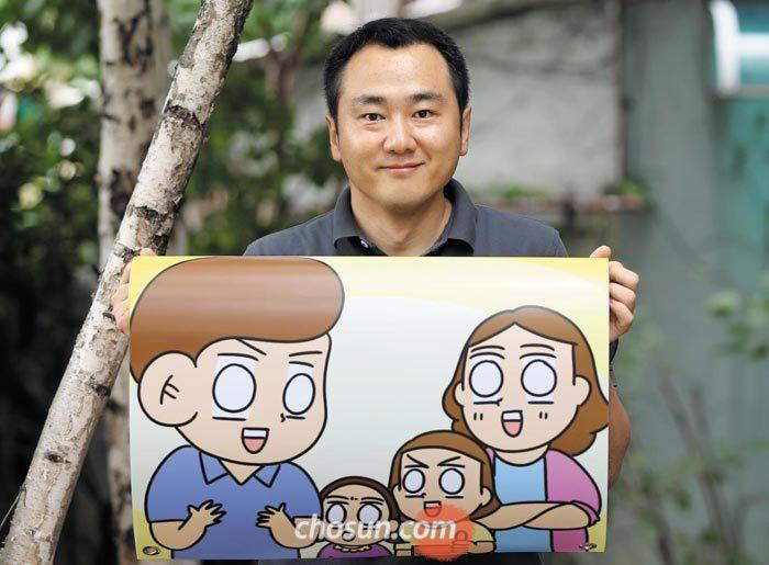 만화가 김양수씨가 서울 풍납동 작업실 앞에서 웹툰'생활의 참견'1000회를 기념하는 인쇄물을 들어 보였다.