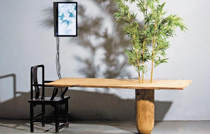 대나무와 원목 테이블, 모니터와 의자로 하나의 풍경을 묘사한 심문섭의'반추'.