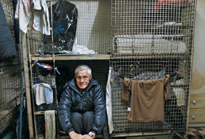 홍콩 외곽의 한 건물 내 구석에 철창을 갖다 놓고 잠자리로 이용하는 한 노인의 모습이다.