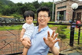 자유한국당 이철우 의원이 최근 구입한 경북 성주 사드 기지 인근 주택 앞에서 손녀와 사진을 찍고 있다.