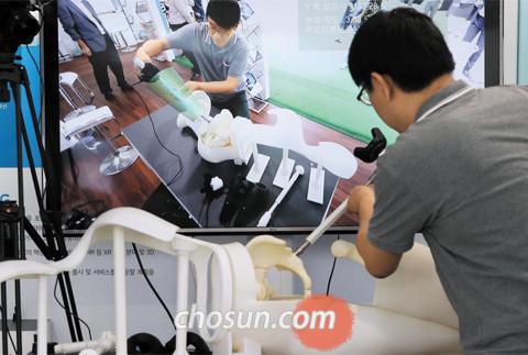 의료용 VR·AR(증강현실) 기술 업체 '솔리드이엔지' 관계자가 인공 고관절 수술을 돕는 VR·AR 시스템을 시연하고 있다. 카메라가 고관절이 삽입되는 각도를 인식해 최적의 삽입 범위를 모니터에 표시해준다.