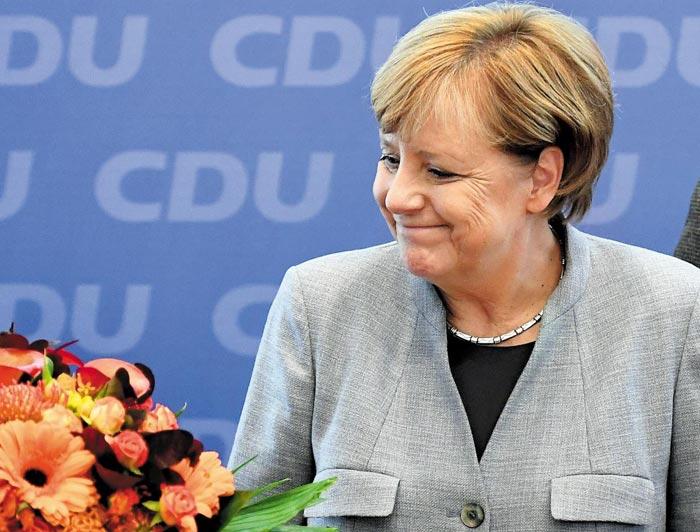 24일(현지 시각) 열린 독일 총선에서 승리한 앙겔라 메르켈 총리가 25일 자신이 이끄는 기독민주당 당사에서 승리를 축하하는 꽃다발을 받으며 웃고 있다.