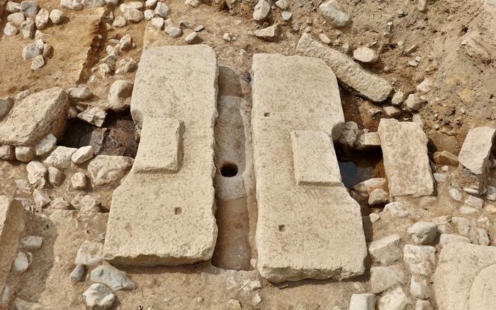 경주 동궁과 월지에서 발굴된 통일신라시대 수세식 화장실. 발판으로 놓은 판석 사이로 타원형의 화강암 변기가 보인다. 변기 아래에는 왼쪽에서 오른쪽으로 흐르는 하수 시설이 있다.