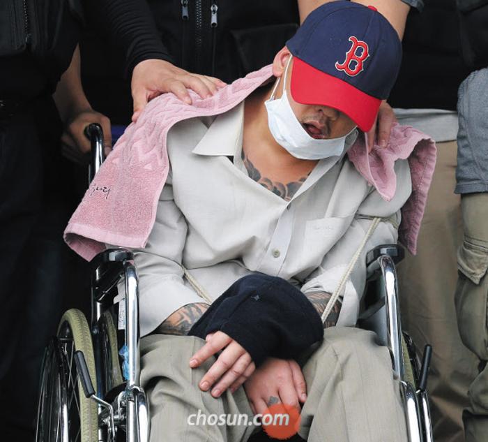 """팔·가슴 등에 문신 딸의 친구를 살해하고, 시신을 야산에 유기한 혐의를 받는 '어금니 아빠' 이모(35)씨가 8일 오후 서울 중랑경찰서에서 조사를 받은 다음 휠체어에 앉아 나오고 있다. 모자와 마스크로 얼굴을 가린 그는 """"살해 혐의를 인정하느냐""""는 취재진의 질문에 아무 대답을 하지 않았다."""