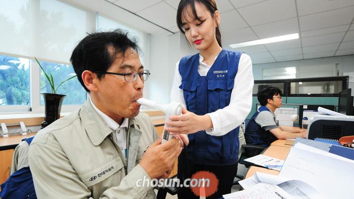 지난달 27일 현대차 울산 4공장에서 김모아(27) 간호사가 같은 공장에 근무하는 직원의 입에 측정기를 대고 일산화탄소(CO) 수치를 체크하고 있다. 현대차 울산공장에서는 지난해부터 대대적인 '담배 끊기' 바람이 불어 현재까지 1000명 넘는 임직원이 금연에 성공했다.