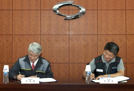 박동훈 르노삼성 사장(왼쪽)과 김효성 노조위원장이 12일 가진 2017년 임금협약 조인식에서 서명하고 있다./르노삼성 제공