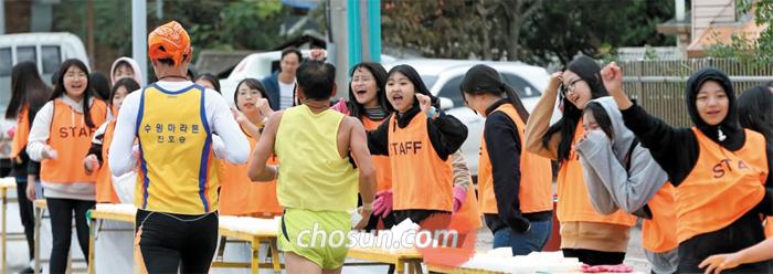 춘천마라톤의 또 다른 주인공은 자원봉사자들이다. 지난해 10월 자원봉사 학생들이 춘천마라톤 37.5㎞ 지점에서 물에 적신 스펀지를 나눠주며 러너들을 응원하는 모습.