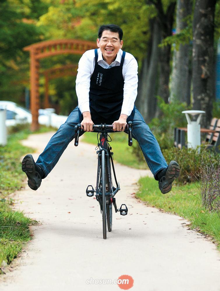 """미대륙횡단자전거대회(RAAM·램) 한국인 최초 우승자 김기중씨가 지난 18일 경북 구미에서 '삼일문고' 앞치마 입고 자전거를 탔다. """"가족이 반대한 램과 달리 서점은 온 시민이 알게 모르게 응원해줘 힘을 얻는다""""고 했다./구미=김종호 기자"""