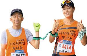 장애인 배테랑 마라토너 김상용씨와 김씨의 눈을 대신해 함께 달리는 가이드러너 김은경씨가 완주를 다짐하는 포즈를 취하고 있다.