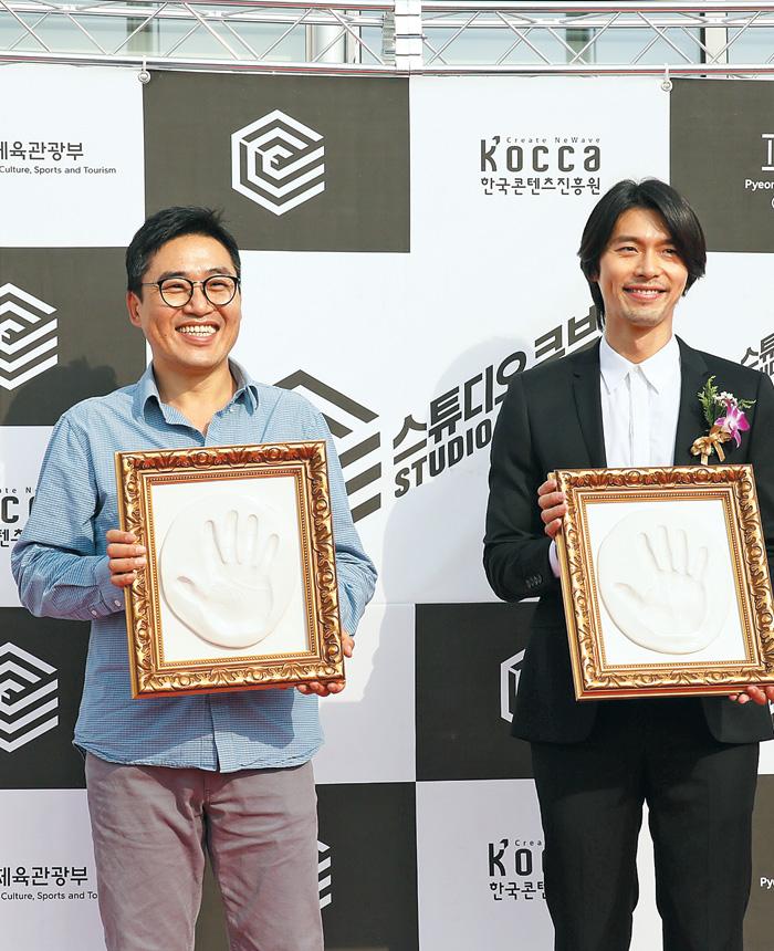 스튜디오 큐브 개관식에 참석한 김성훈 영화감독과 배우 현빈이 핸드프린팅을 하고 있다