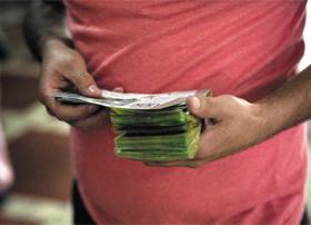 사람들은 로또가 희망인데… - 지난달 25일 베네수엘라 수도 카라카스에서 한 시민이 수탉 등을 상품으로 주는 '동물 복권'을 사기 위해 돈을 세고 있다. 극심한 인플레이션으로 화폐가치가 폭락한 베네수엘라에서는 복권 한 장을 사기 위해 한 뭉치의 지폐가 필요하다.