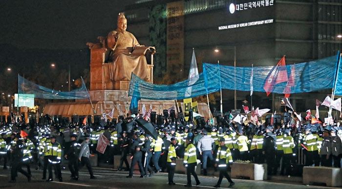 7일 밤 서울 광화문광장에 있던 반미 시위대가 트럼프 대통령 차량이 지나갈 것으로 예상한 세종문화회관 앞 도로 쪽으로 쓰레기를 던지자 경찰이 그물망을 펼쳐 이를 막고 있다.