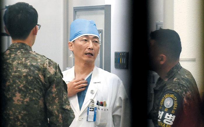 13일 오후 경기도 수원 아주대병원 경기남부권역외상센터장인 이국종(가운데 수술복을 입은 이) 교수가 군 관계자와 대화하고 있다.