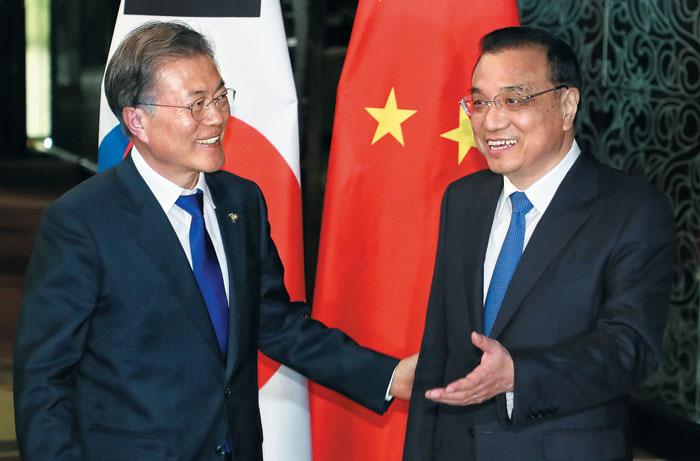 문재인(왼쪽) 대통령이 13일(현지 시각) 오후 아세안 정상회의가 열리는 필리핀 마닐라에서 리커창(李克强) 중국 총리와의 회담에 앞서 인사를 나누고 있다