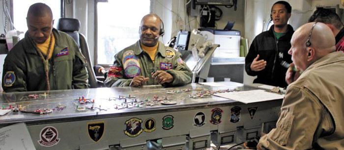 동해에서 진행된 한·미 연합 훈련에 참가한 로널드 레이건함(CVN-76) 관계자들이 지난 13일 갑판 통제실에서 전투기 배치 등 갑판 위 상황을 모형으로 나타내는 상황판에 대해 설명하고 있다.