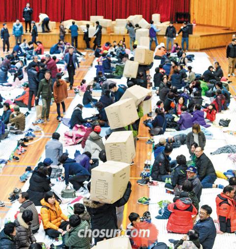 주민 대피소엔 추위 견딜 모포가… - 역대 2위 규모의 지진이 발생한 15일 오후 경북 포항시 북구 흥해실내체육관으로 대피한 주민들이 모포가 담긴 박스를 옮기고 있다.