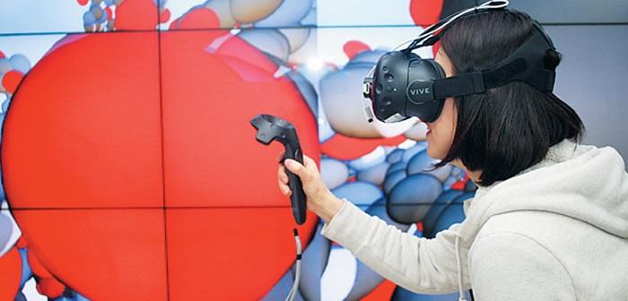 한 여성이 장비를 착용하고 가상현실 세계와 사람이 실제 살고 있는 세계를 연결하는 '공존 현실 기술'을 체험하고 있다.