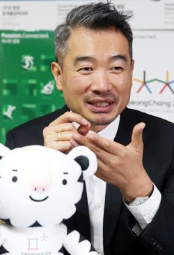 양정웅 연출가가 평창 동계올림픽 캐릭터 인형을 앞에 놓고 활짝 웃고 있다.