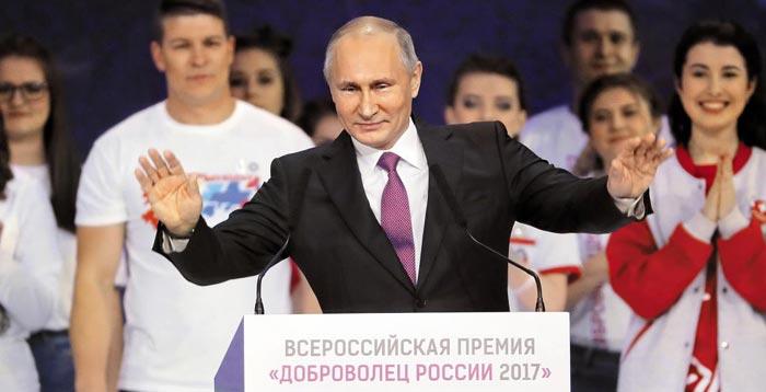 푸틴 대통령이 7일 오전 모스크바에서 열린'러시아 자원봉사자 포럼'행사에 참석해 박수를 보내는 참석자들에게 두 손을 들어 답례하는 모습.