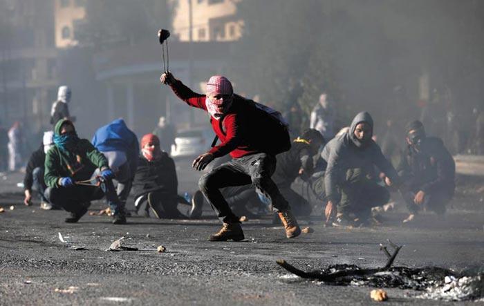 8일(현지 시각) 팔레스타인 서안 지구의 최대 도시인 라말라에서 벌어진 반미(反美) 시위에서 얼굴을 가린 팔레스타인 시위대가 이스라엘군을 향해 슬링(투석 끈)을 이용해 돌을 던지고 있다.