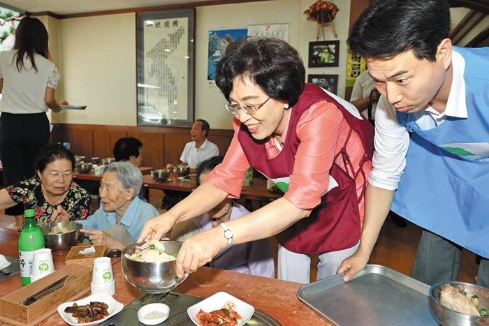 """박춘희 송파구청장이 지난 8월 '어르신 삼계탕 드리기' 행사에서 음식을 나르고 있다. 한때 분식집 주인이었던 박 구청장은 """"누군가에게 따뜻한 밥을 해주는 건 행복한 일""""이라고 했다."""