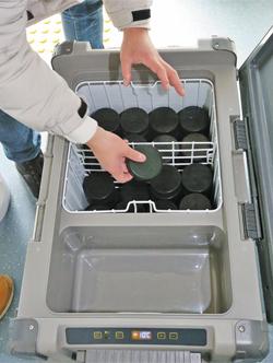 20일 강원도 강릉하키센터에서 조직위 매니저가 이동식 냉동고에 퍽을 넣고 있는 모습.