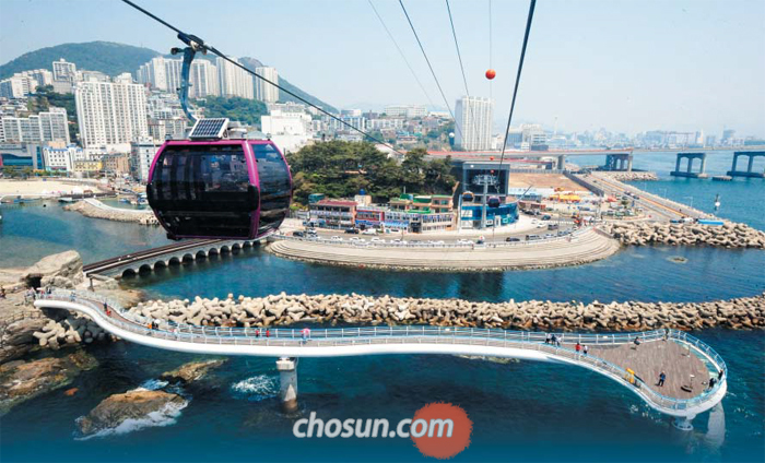 부산 서구 송도해수욕장을 가로지르는 해상케이블카가 송도 앞바다 위를 오가고 있다. 방파제와 바다가 어우러진 풍광에 하루 탑승객 1만1000명이 몰린다.
