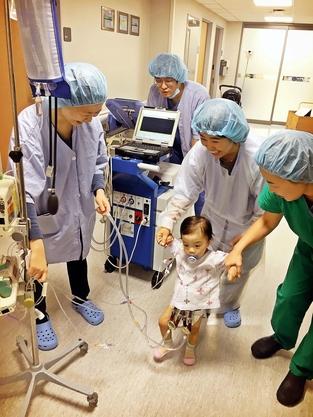 인공심장 이식 환아가 의료진과 함께 보행 운동을 하고 있다. / 세브란스병원 제공
