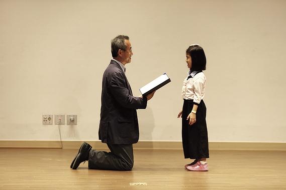 쭈뼛거리며 서있는 작은 여자 아이 앞에 무릎을 꿇은 최재천 교수. 2016년 5월, '우리 들꽃 포토에세이 공모전' 시상식에서./사진 제공=메디치