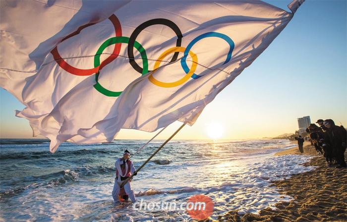 새해 첫날 아침. 강원 강릉시 경포해변에서 풍물연구소 회원이 떠오르는 태양을 배경으로 평창올림픽 성공 개최를 기원하며 오륜마크가 그려진 거대한 깃발을 흔들었다. 해돋이를 보러 온 관광객들은 이 모습을 카메라에 담았다.