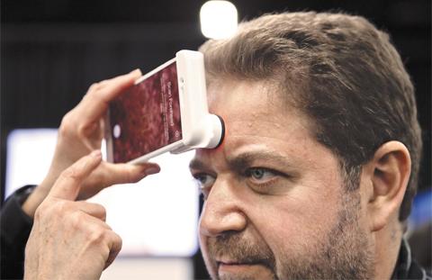 7일(현지 시각) 세계 최대 IT(정보기술) 전시회 'CES 2018' 사전 공개 행사에서 한 참석자가 뉴트로지나의 피부 분석기로 자신의 피부 상태를 체크하고 있다.