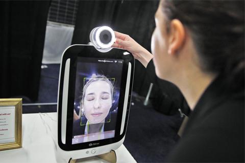 'CES 2018' 사전 공개 행사에서 한 참석자가 대만의 전자 업체 뉴킨포가 개발한 스마트 뷰티 거울 '하이 미러'로 자신의 피부 상태를 체크하고 있다.